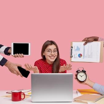 Brünette frau, die am schreibtisch sitzt, umgeben mit gadgets und papieren