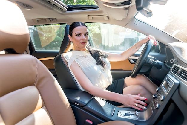 Brünette frau, die automatikgetriebehebel im auto verschiebt