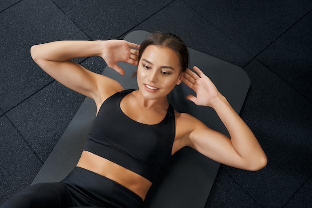 Brünette frau, die bauchmuskeln auf schwarzer matte im fitnessstudio tut