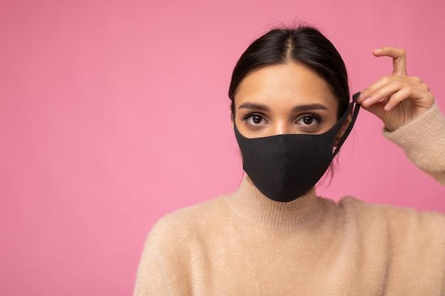 Brünette frau, die eine anti-virus-schutzmaske trägt, um andere vor einer infektion mit corona covid-19 und sars cov 2 einzeln auf rosafarbenem hintergrund zu schützen. platz kopieren