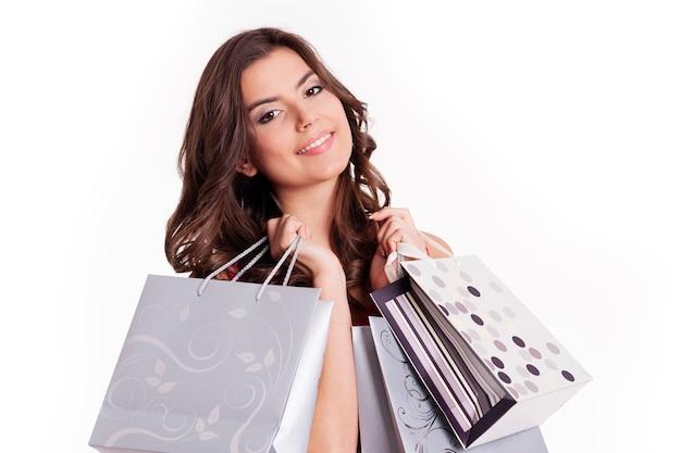 Brünette frau, die einkaufstaschen neben ihrem gesicht hält