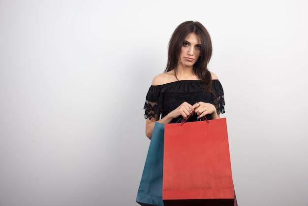 Brünette frau, die einkaufstaschen trägt.