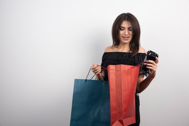 Brünette frau, die einkaufstüten und kaffeetasse hält.