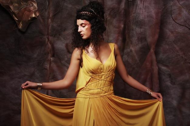 Brünette frau, die gelbes abendkleid trägt