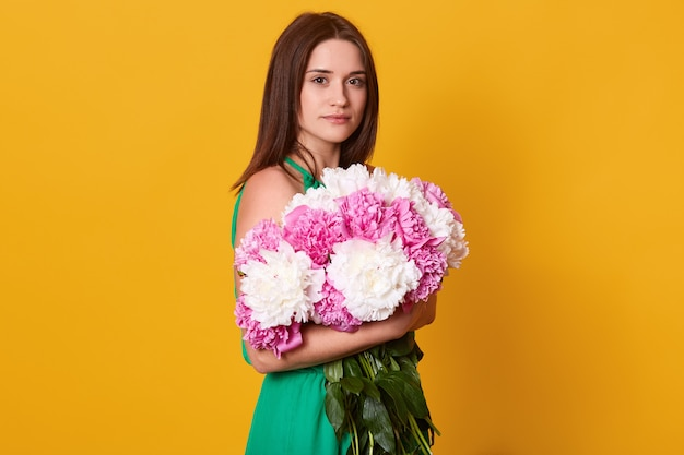 Brünette frau, die großen blumenstrauß mit rosa und weißen pfingstrosen umarmt, stilvolle frau mit blumen, hat ruhigen gesichtsausdruck und posiert isoliert auf gelb.