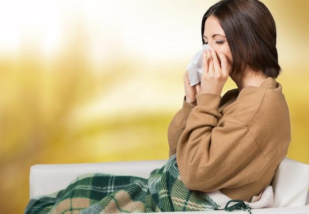 Brünette frau, die im wohnzimmer in ein taschentuch niest