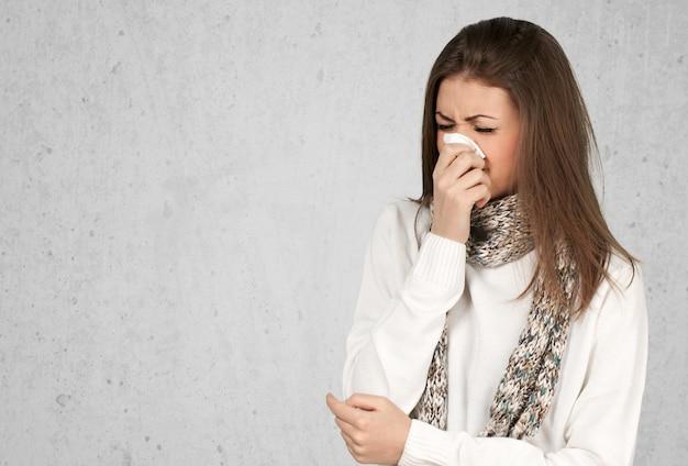 Brünette frau, die in ein taschentuch niest