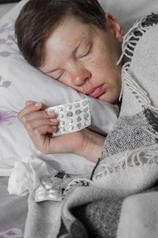 Brünette frau, die in ihrem bett unter karierter decke mit pillen schläft