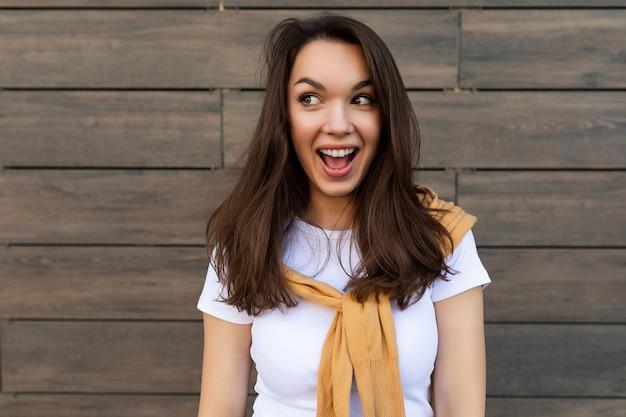 Brünette frau, die lässiges weißes t-shirt und jeans mit gelbem pullover trägt, der nahe brauner wand in der straße bereitstellt und spaß hat.