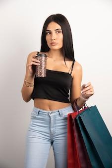 Brünette frau, die mit einkaufstüten und kaffee aufwirft. hochwertiges foto