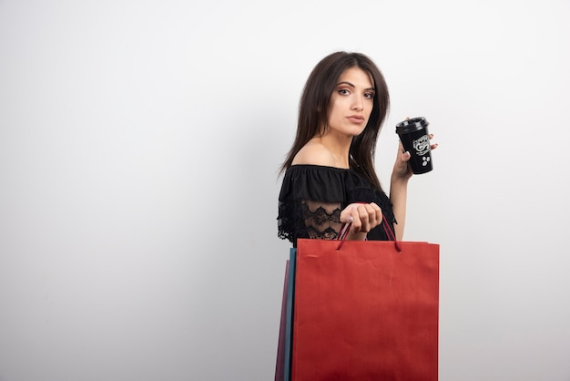 Brünette frau, die mit einkaufstüten und kaffeetasse aufwirft.