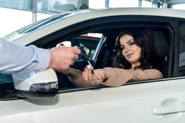 Brünette frau, die schlüssel von neuem auto nimmt