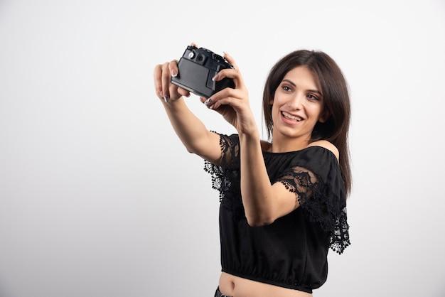 Brünette frau, die selfies mit kamera nimmt