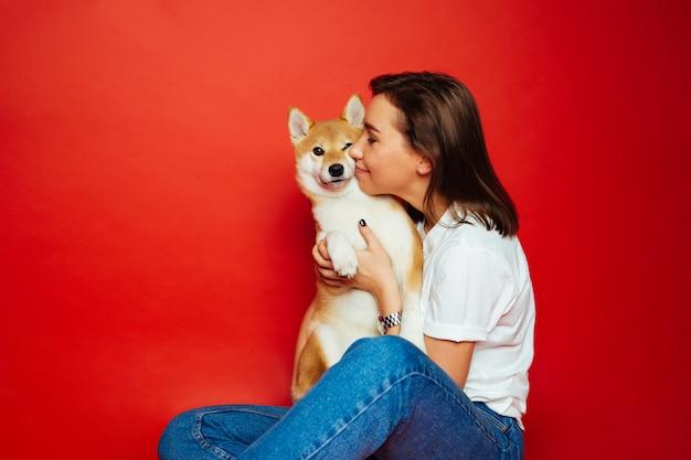 Brünette frau, die shiba inu hund umarmt und küsst, roter hintergrund. liebe haustiere
