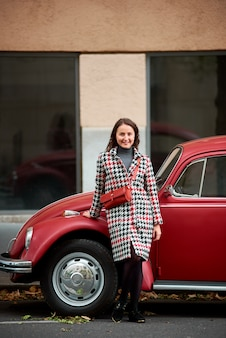 Brünette frau, die sich auf rotes retro-auto stützt und kamera mit lächeln betrachtet