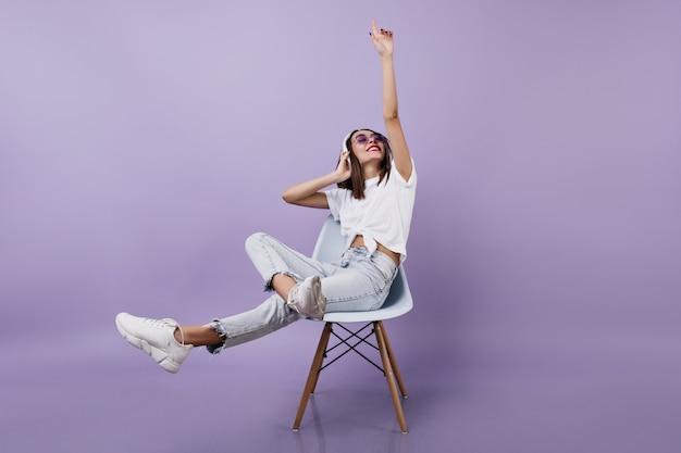 Brünette frau, die spaß hat und musik hört. gut gekleidete junge dame in kopfhörern, die auf stuhl sitzen.