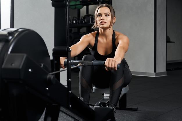Brünette frau, die übung mit ausrüstung im fitnessstudio macht