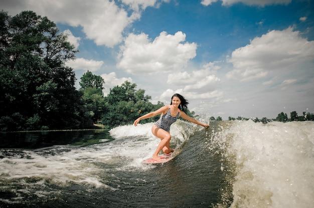 Brünette frau, die wakeboard auf welle des motorboots reitet