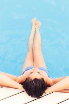 Brünette frau im badeanzug auf dem pool allein entspannend. sommer. draußen