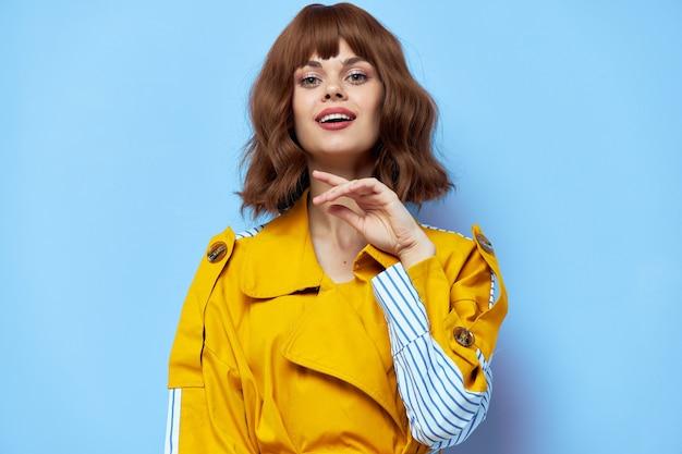 Brünette frau im gelben mantel gestikuliert mit händen auf blau