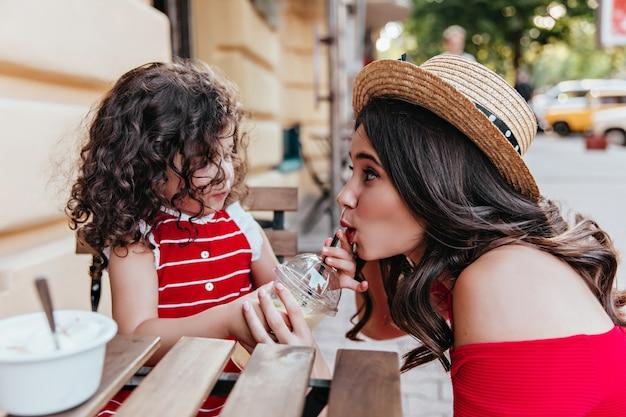 Brünette frau im strohhut, die spaß mit tochter im café hat. nettes kleines mädchen, das mutter beim sitzen im restaurant im freien betrachtet.