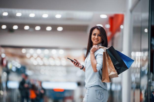 Brünette frau im supermarkt mit vielen paketen und telefon in den händen hat einkaufstag.