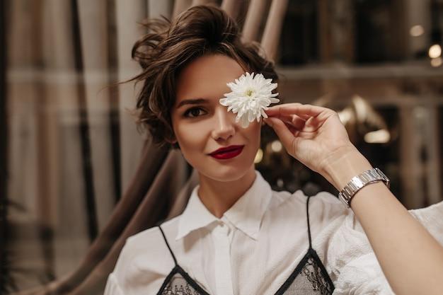 Brünette frau in den weißen kleidern, die mit heller blume innen aufwerfen. nette frau mit kurzer gewellter frisur und rotem lippenstift im café.