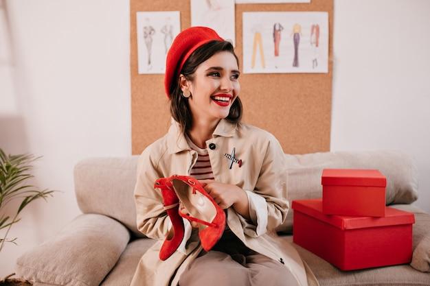 Brünette frau in der roten baskenmütze, die schuhe der hohen absätze hält. hübsche frau mit hellem hut und langem umhang sitzt auf dem sofa und entspannt sich.