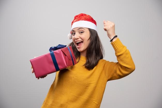 Brünette frau in der weihnachtsmannmütze, die ihre faust zeigt und geschenkbox hält.