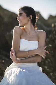 Brünette frau in einem weißen kleid mit einem aufrichtigen lächeln