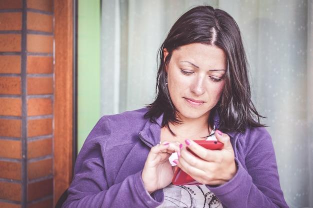 Brünette frau in einer lila jacke mit einem smartphone