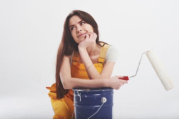 Brünette frau in gelber uniform sitzt gegen weiße wand im studio