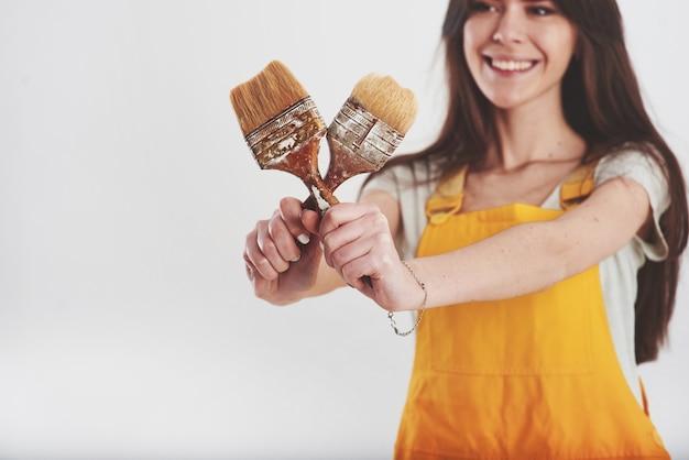 Brünette frau in gelber uniform steht gegen weiße wand im studio