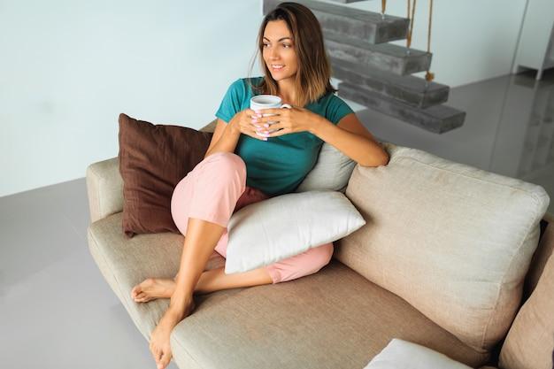 Brünette frau in gemütlicher hauskleidung, die tasse tee hält, fenster betrachtet und sich auf modernem sofa entspannt