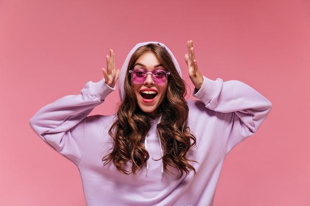 Brünette frau in lila übergroßem hoodie schaut auf rosa wand in die kamera