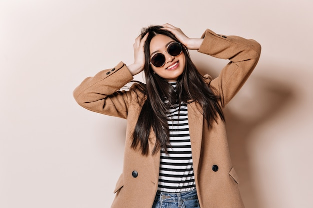 Brünette frau in sonnenbrille und mantel kräuselt ihre haare
