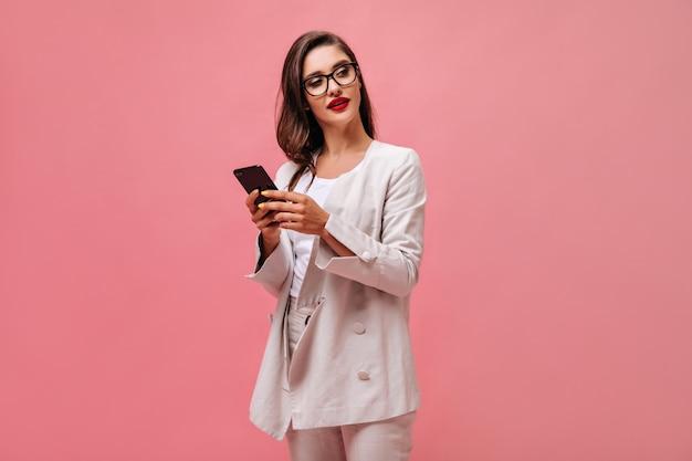 Brünette frau in stilvollem outfit und brillen posiert mit smartphone. junge geschäftsfrau mit roten lippen und im weißen anzug hält telefon.
