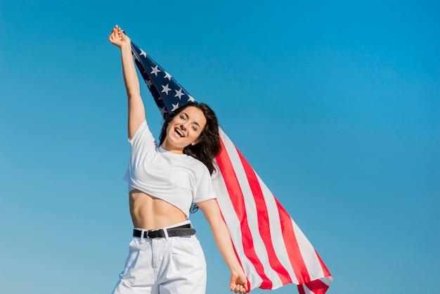 Brünette frau in weißen kleidern, die große usa-flagge halten