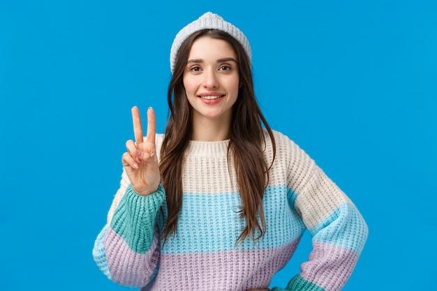 Brünette frau in wintermütze und pullover zeigt friedenszeichen und lächelt