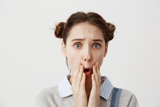 Brünette frau ist zutiefst traurig über schreckliche neuigkeiten, die den offenen mund mit den händen bedecken. weibliche person mit haaren in doppelbrötchen in frustration kann nicht an trauer glauben.