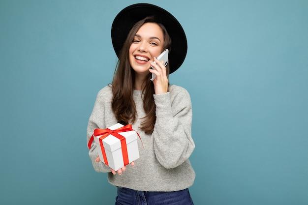 Brünette frau lokalisiert über blaue hintergrundwand, die stilvollen schwarzen hut und grauen pullover hält, die geschenkbox hält, die auf smartphone spricht und kamera betrachtet.