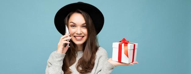 Brünette frau lokalisiert über blaue hintergrundwand, die stilvollen schwarzen hut und grauen pullover hält geschenkbox hält, die auf smartphone spricht und kamera betrachtet.