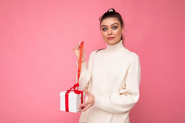 Brünette frau lokalisiert über rosa hintergrundwand, die weißen pullover hält, der geschenkbox und unboxing-geschenk hält, das kamera betrachtet.
