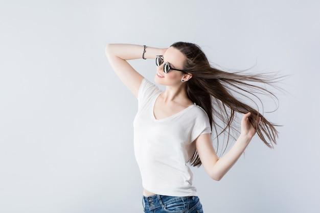 Brünette frau mit flatternden haaren und sonnenbrille