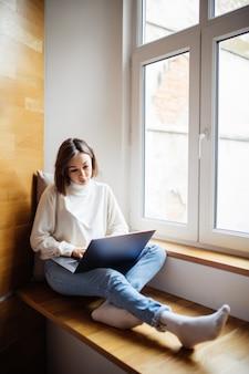 Brünette frau mit kurzen haaren arbeitet am laptop, während sie in der täglichen zeit auf einem breiten fensterhügel sitzt