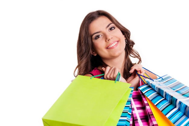 Brünette frau mit mehrfarbigen einkaufstaschen
