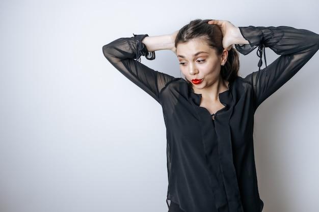 Brünette frau mit roten lippen berührt ihren kopf