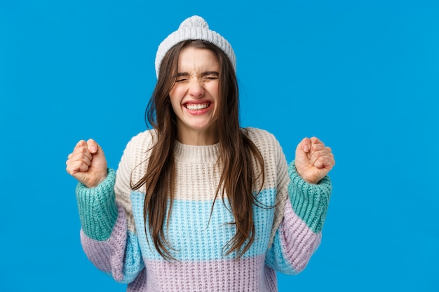 Brünette frau mit wintermütze und pullover aufgeregt