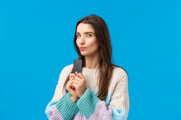 Brünette frau mit winterpullover hält kreditkarte