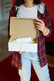 Brünette frau öffnet, online-bestellpaket mit kosmetik zu hause in der hand halten, weibliche kundin freut sich über online-shopping, geliefertes konzept.